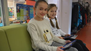 Två flickor med pekplattor sitter på en soffa.