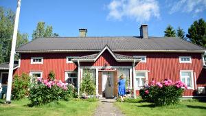 En gammal bondgård med vita knutar med en grönskande trädgård framför. En kvinna i blå klänning syns gå mot husets ingång.
