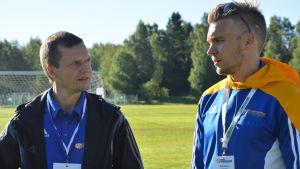 Johan Byholm och Putte Lindroos stpr bredvid varandra och talar på en fotbollsplan. De bär båda fotbollskläder.