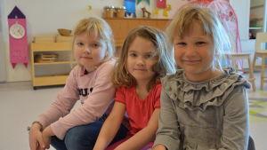 Tre flickor sitter på en bänk.