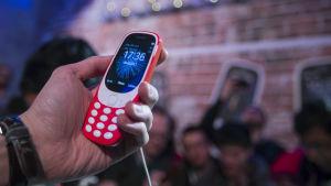 Hand som håller i röd mobiltelefon