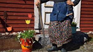 Bild från magen och neråt på en pseron som står klädd i ett arbetsförkläde sytt av jeans och regnrock, med en trädgårdsgrep i handen, bredvid en hink med vita vårblommor.