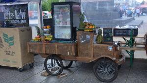 en kärra med en massa frukter såsom ananas, banan och apelsiner