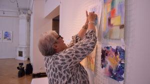 Camilla Ramstedt hänger akvareller på väggen