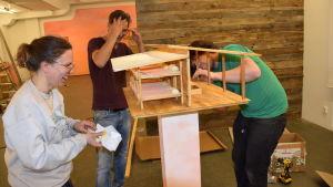 Dafna Maimon, Jonatan Habib-Engqvist och Ethan Hayes-Chute bygger ihop miniatyrmodellen av Camp Solong