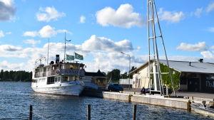 Båten Sunnan vid kajen, en gammal magasinbyggnad i bakgrunden.