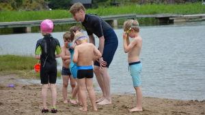 Simskolelärare Anton Ristimäki uppmuntrar barnen att våga sig i vattnet.