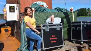 En teje och en kille bär en stor låda på en båt.