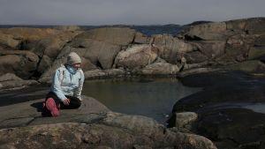 Nainen istuu kalliolla saarella. Takana näkyy pieni laguuni, kalliota ja niiden takana siintää meri ja horisontti. Naisella on päällään toppatakki, pipo ja pinkit kumisaappaat.