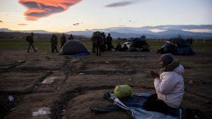 Asylsökande som inte släpps in i Makedonien sitter och ber på den grekiska sidan om gränsen 2.12.2015