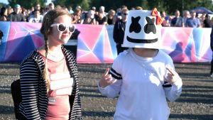 Två besökare på Weekend Festival trivs i solskenet. Den ena har klätt sig helt i vitt, precis som idolen Marshmello.