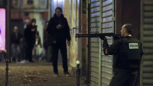 En polis letar efter gärningsmännen utanför restaurangen Le Petit Cambodge.