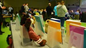 I förgrunden böcker och i bakgrunden människor på ett seminarium.