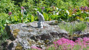En staty av en örn sitter i ett stenparti i Engströms trädgård.