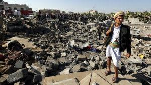 Huthirebell står vakt på ett område i Sanaa där Saudiarabien har utfört flygattacker.