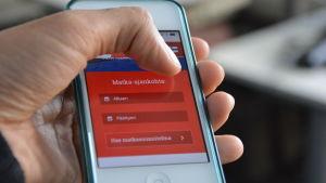 En hand håller i en mobiltelefon.