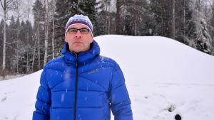 Hannu Riiki, ordförande för Malax IF Skidning, står framför en stor hög med snö.
