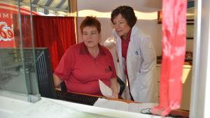 Leena och Marina Furubacka tittar på datorn i deras privata läkarmottagning i Nedervetil