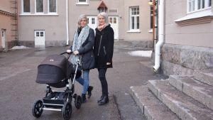Två kvinnor med en barnvagn framför stenbyggnad.