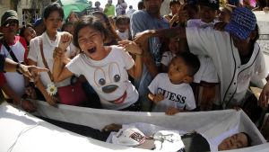 Över 3 000 människor har dödats sedan Rodrigo Duterte ínledde sin brutala kampanj mot narkotingalangare och droganvändare.  Här sörjer anhöriga en misstänkt narkotikaförsäljare som sköts ihjäl i Manila