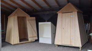 Två nybyggda badhytter står omålade under ett tak. Emellan dem står en slags solstol som är målad vit.