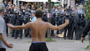 Demonstrant utan skjorta står med armarna ute. I bakgrunden ser man många poliser.