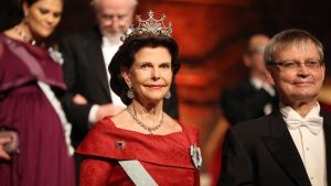 Drottning Silvia och Carl-Henrik Heldin, ordförande för Nobelstiftelsen, anländer till Nobelbanketten 2015.