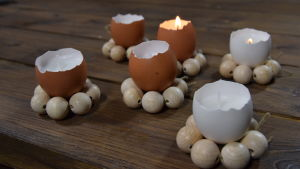 Ljushållare av äggskal och träkulor på ett bord.