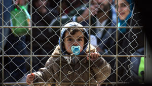 Flyktinbarn tillsammans med andra flyktingar bakom stängsel vid gränsen mellan Grekland och Makedonien.
