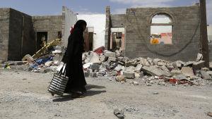 Kvinna går förbi ett hus som förstörts i en saudiledd lufträd.