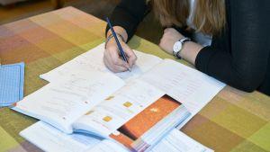 Flicka i högstadieåldern gör läxor.