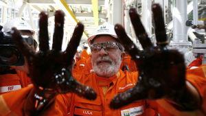 """Luiz Inacio """"Lula"""" da Silva poserar med olja på händerna vid ett Petrobras-jippo i oktober 2010."""
