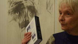 kvinna med bok framför teckning av ansikte