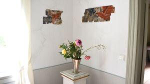 Bitar av 1700-tals tapet har hängts upp på väggen som konst.