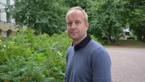 Staffan Åberg poserar i närheten av en buske.