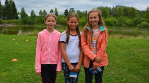 simeleverna evelina björkgren, moah kronholm och amanda nyholm står på gräset framför toby simgrop