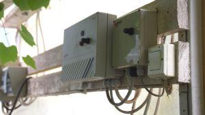 Apparat som kontrollerar vädringsluckor i ett växhus. Den består av vita lådor med några knappar på som man kan vrida på. De är fastsatta på bräder på en vägg.