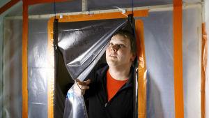 Sami Huuskonen kurkistaa muovisuojan läpi.