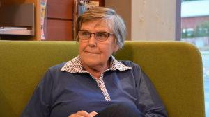 Anne Borg lyssnar på Pentti Vähätalo då han läser i Kimito biblioteket.