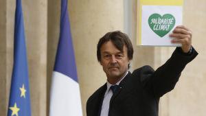 Nicolas Hulot håller upp en skylt med ett grönt hjärta med texten solidaritet för klimatet.