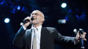 Phil Collins sjunger på scen.
