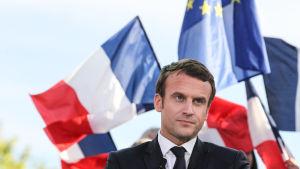 Emmanuel Macron med Frankrikes och EU:s flaggor bakom sig.