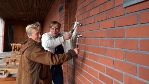 Läraren Margareta Nyman-Klemets och rektorn Mikael Pietilä börjar riva Bergö gamla skola.