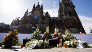 Blomsterhyllningar för flygoffren vid katerdralen i Köln.