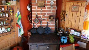 Mökkikeittiö, jossa vanha puulämmitteinen rautahella, valurautapannuja, maustehyllykkö ja muuta keittiötarpeistoa.
