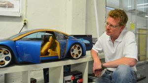 Pasi Pennanen visar ett arbete han gjorde redan år 1997, en bil med en sorts trästomme.