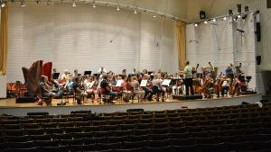 En kammarorkester övar på scen.