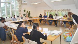 Studerande vid Lärkkullas svenskalinje lyssnar på lärare Sari Huuskonen (till höger).