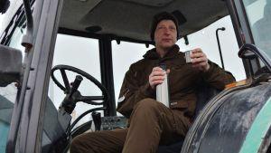 Jordbrukare dricker ur termos i sin traktor.