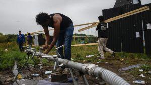 """En man tvättar händerna i flyktinglägret """"Djungeln"""" i Calais Frankrike"""